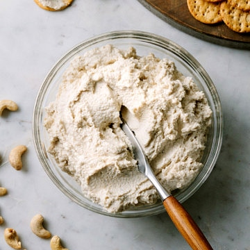 vegan cashew ricotta cheese in a bowl with wooden butter knife