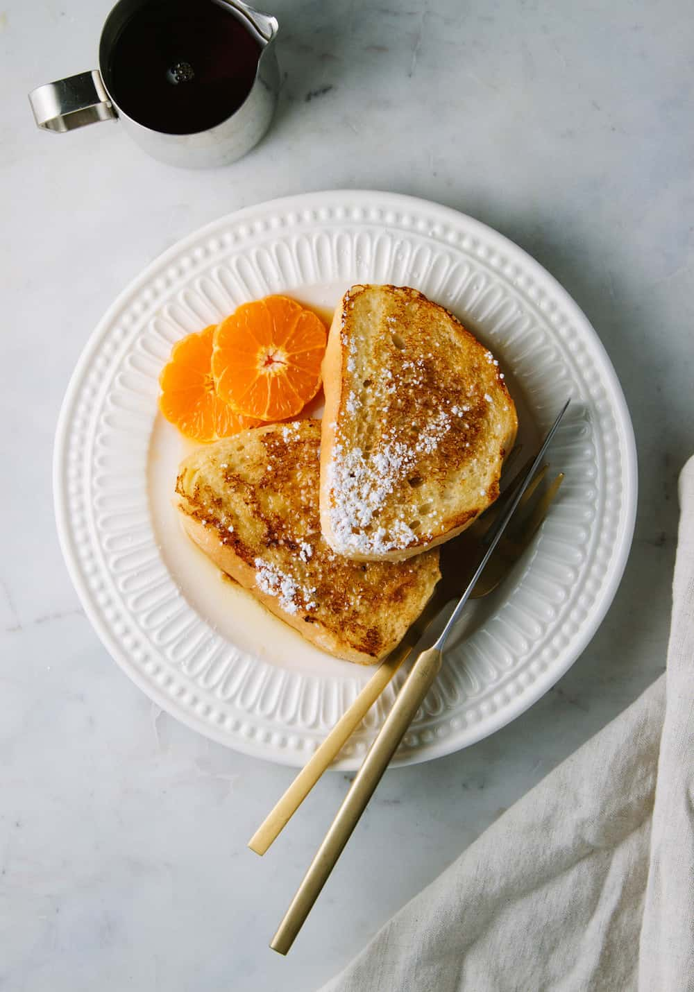 golden orange french toast on a white ceramic plate with maple syrup and orange slices