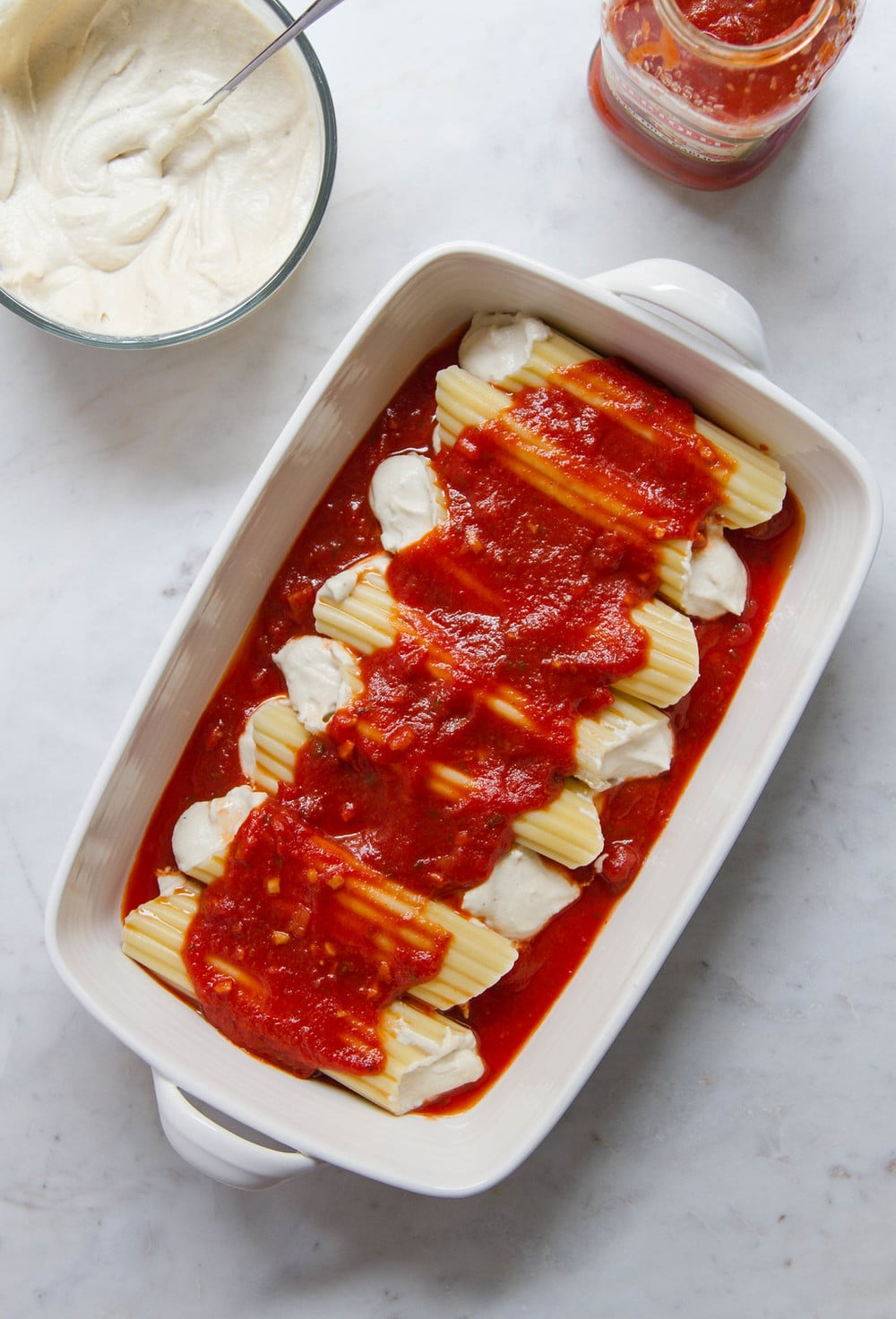 top down view of rectangular baking dish with freshly cooked and filled manicotti shells with cashew ricotta cheese and topped with pasta sauce