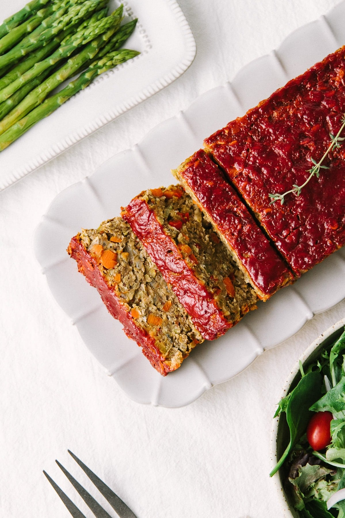 top down view of vegetable lentil loaf cut into slices on a serving platter surrounded by side dishes.