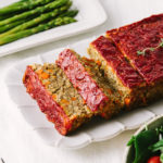 side angle view of vegetable lentil loaf cut into slices on a serving platter surrounded by side dishes.
