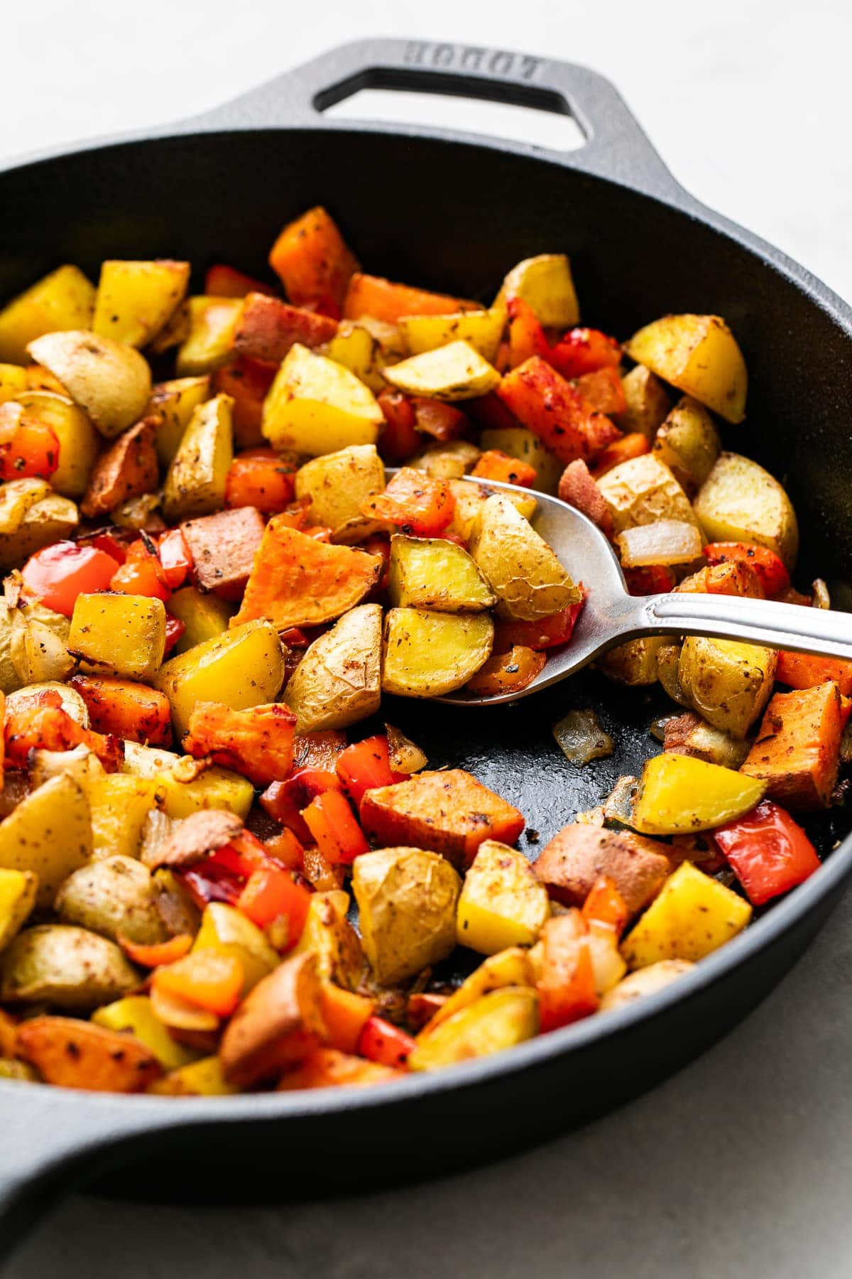 side angle view of freshly made gold and sweet potatoes in a skillet.