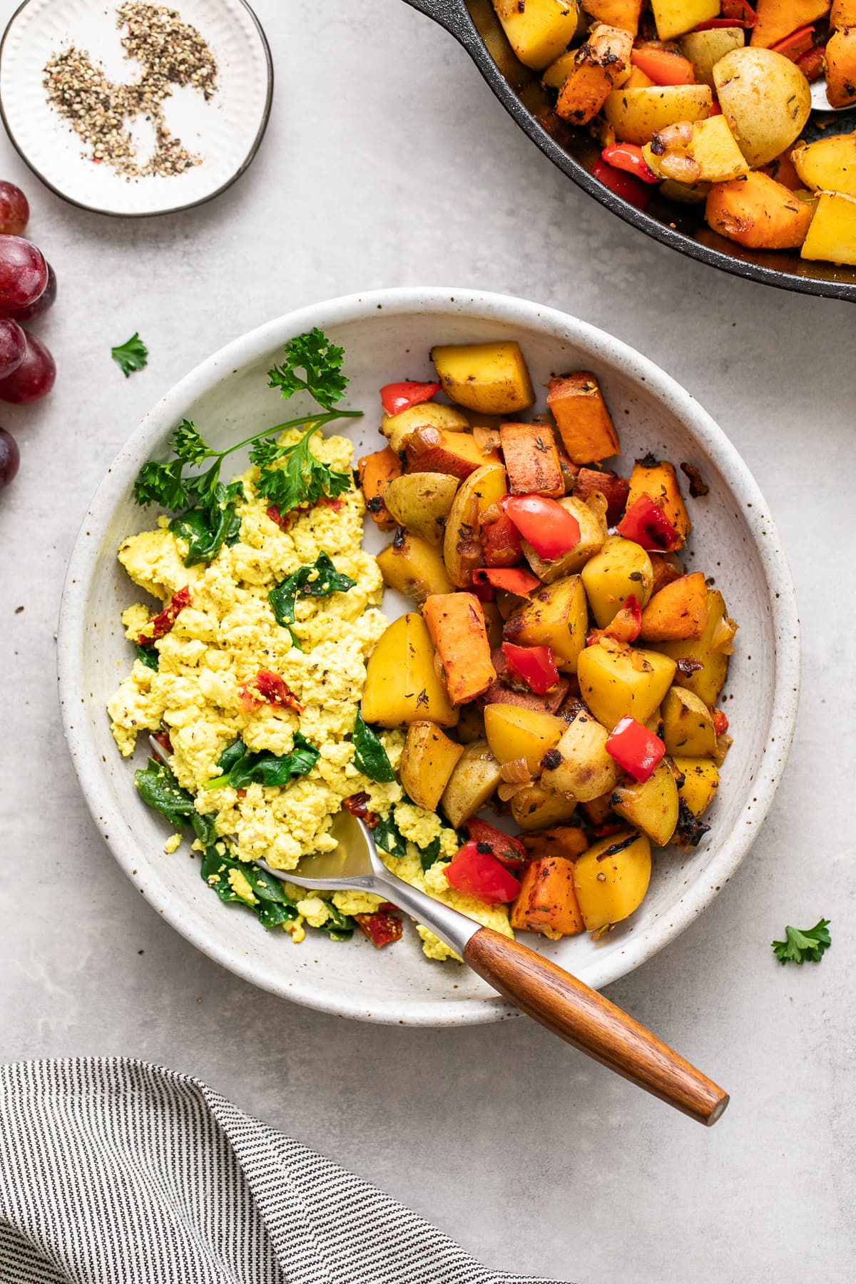 top down view of a bowl with serving of home fries and tofu scramble with items surrounding.