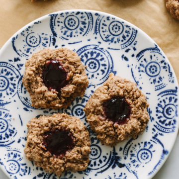 oat jam thumbprint cookies on a small blue and white plate