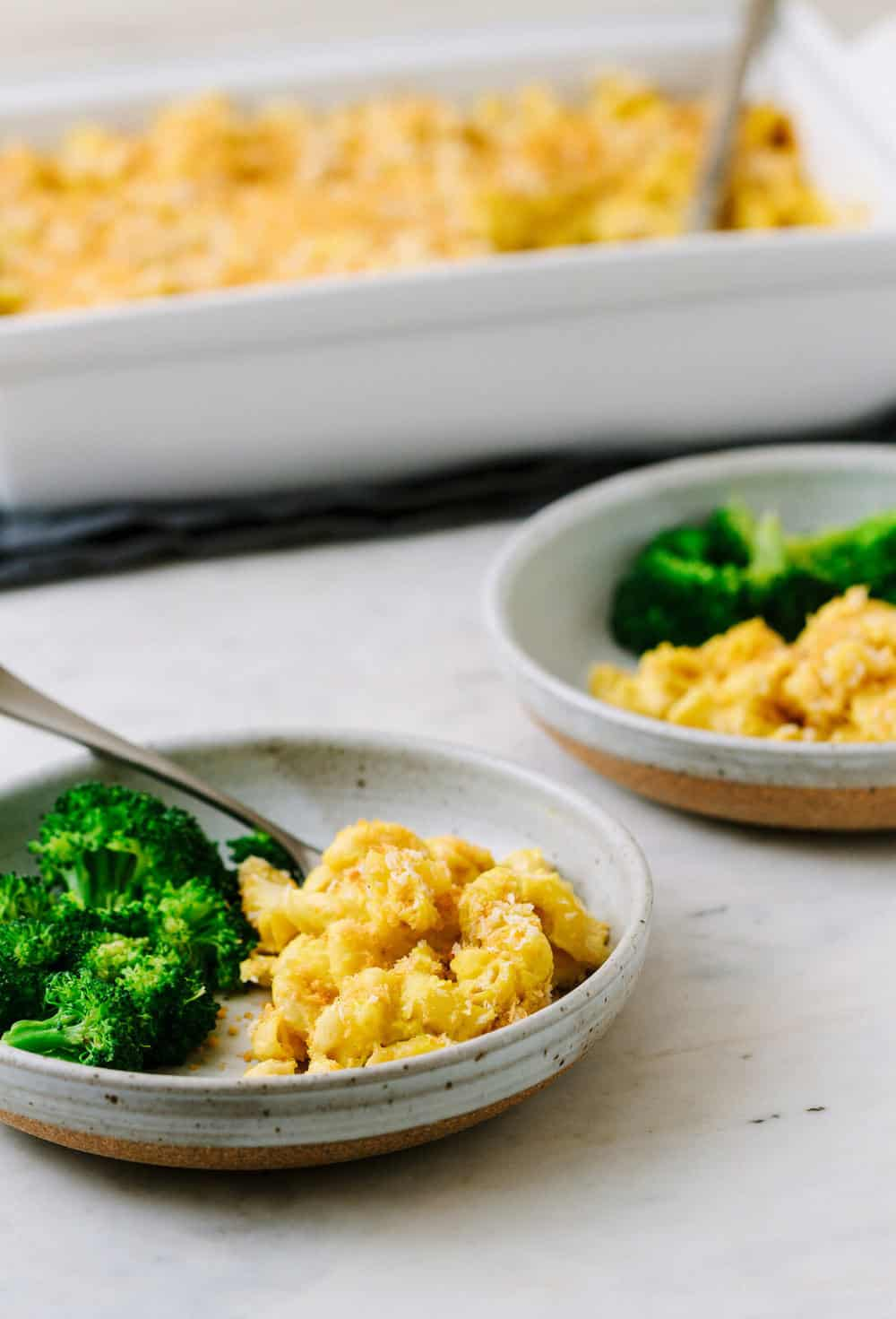 creamy vegan mac and cheese bake in a bowl with steamed broccoli