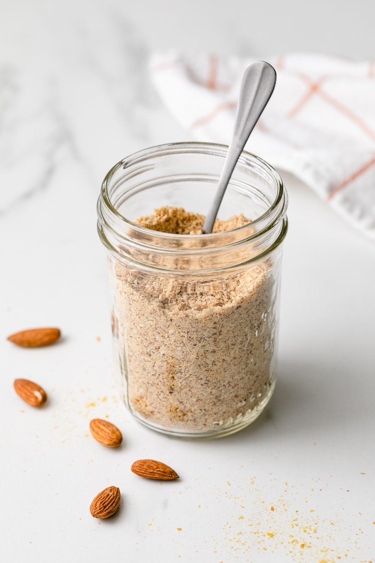 side angle view of almond parmesan in a mason jar with spoon.