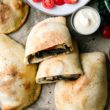 top down view of vegan calzone cut in half with items surrounding.