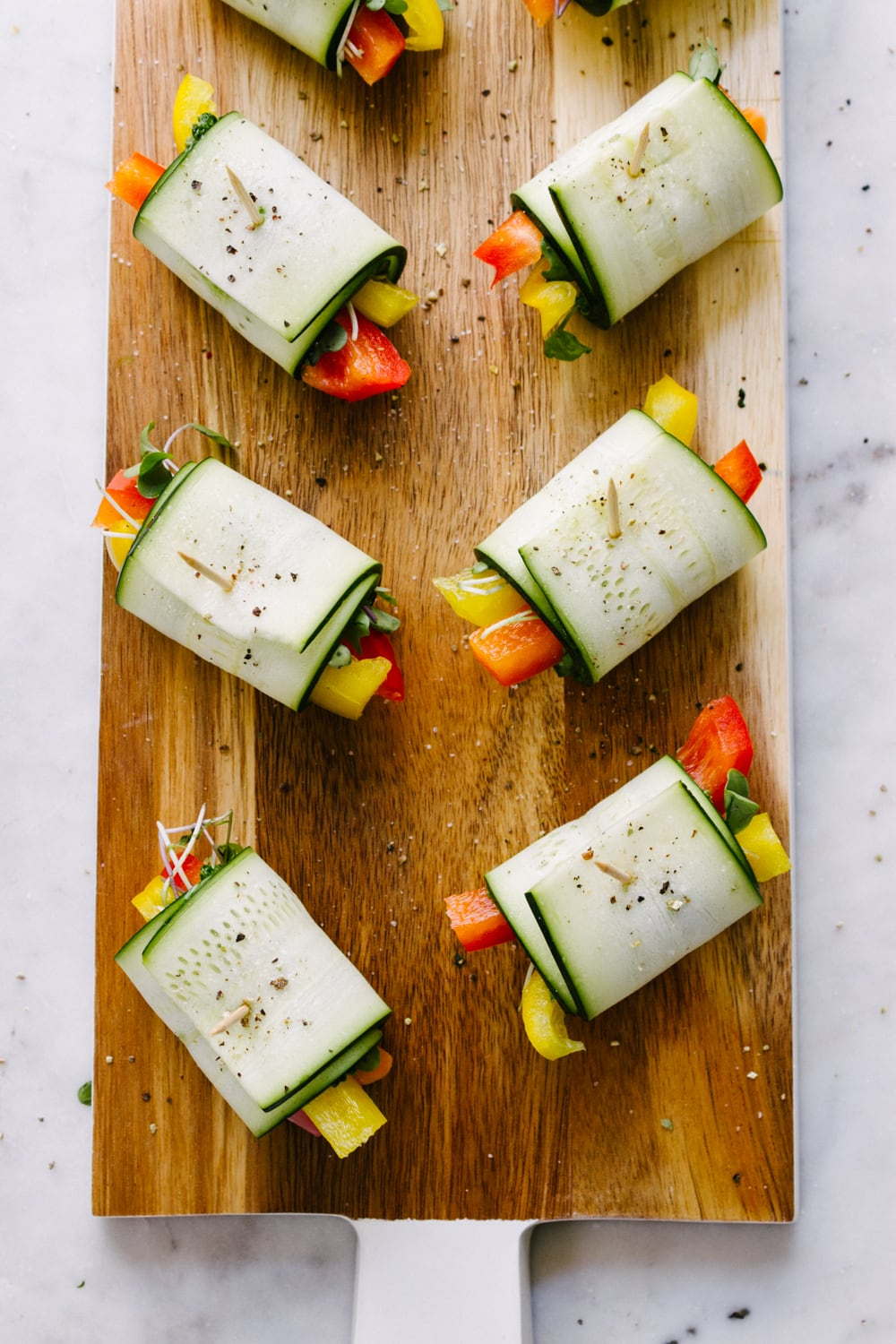 a top down view of a group of raw zucchini wraps filled with fresh bell peppers, carrots, kale pesto and micro greens freshly made and sitting on a wooden serving board