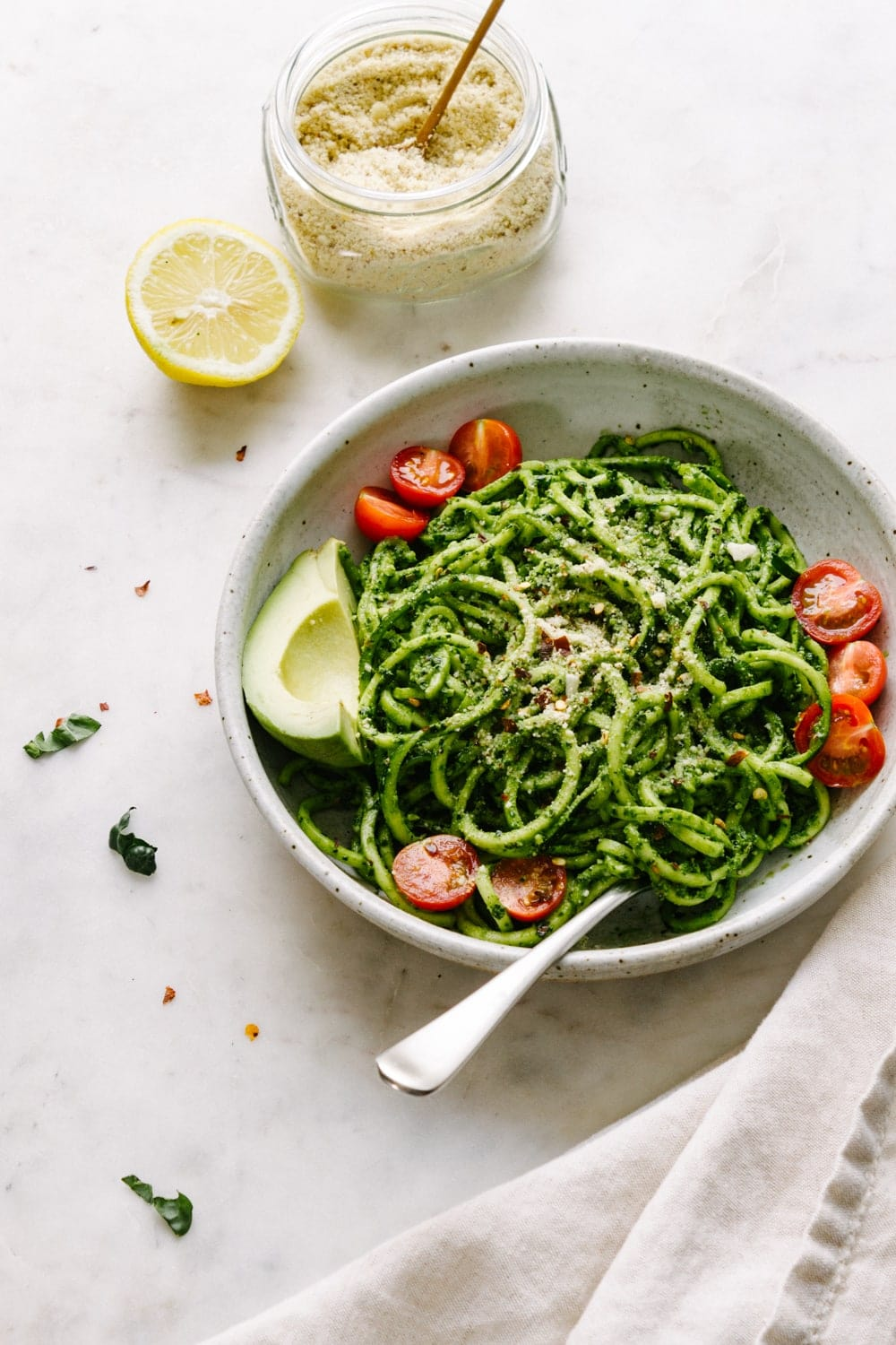 a side view of a bowl of zucchini noodles tossed with spicy kale pesto