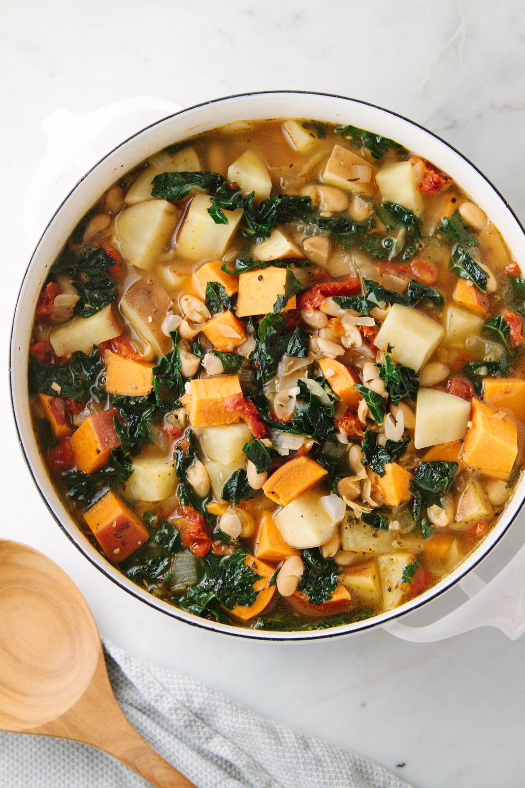 top down view of a pot with healthy sweet potato and kale soup.