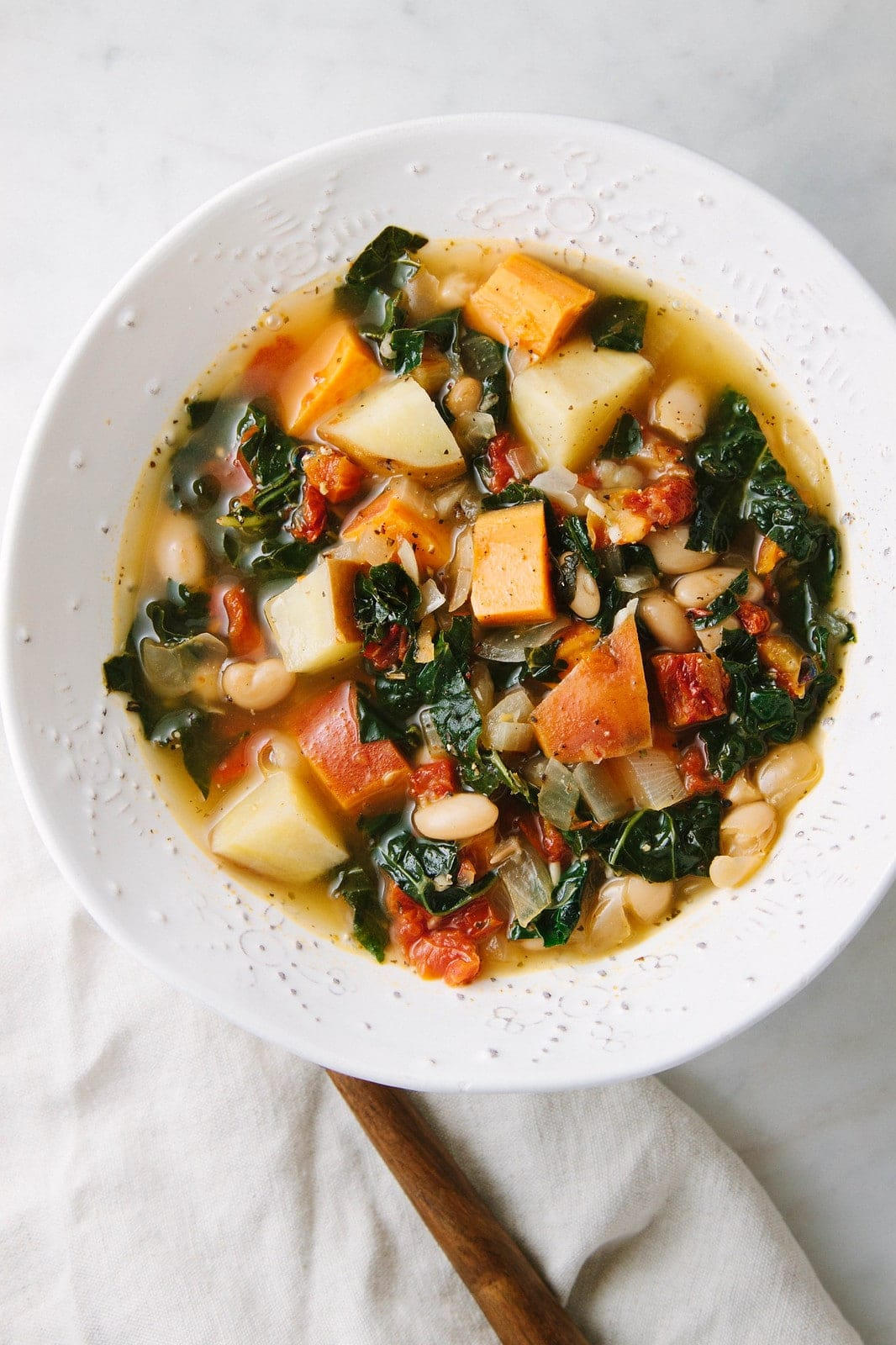 top down view of a bowl with sweet potato and kale soup with white beans.