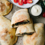 top down view of freshly made mushroom and kale vegan calzones on a parchment paper with items surrounding.