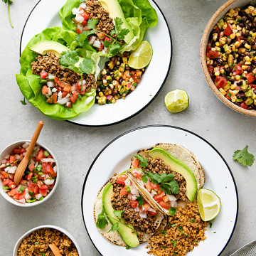 top down view of vegan street tacos on white plates with items surrounding.