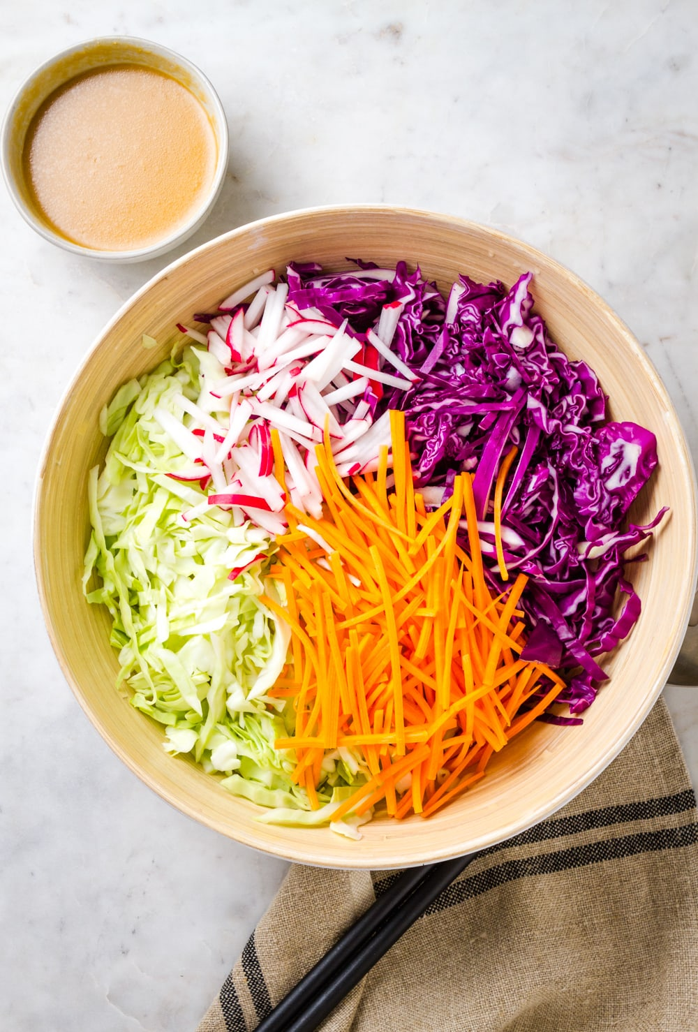 top down view of a mixing bowl with ingredients added for making slaw salad just before mixing.