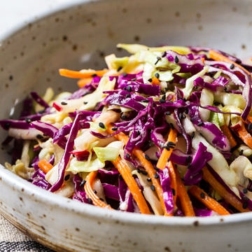 side angel view of a rustic bowl filled with a serving of colorful asian slaw salad