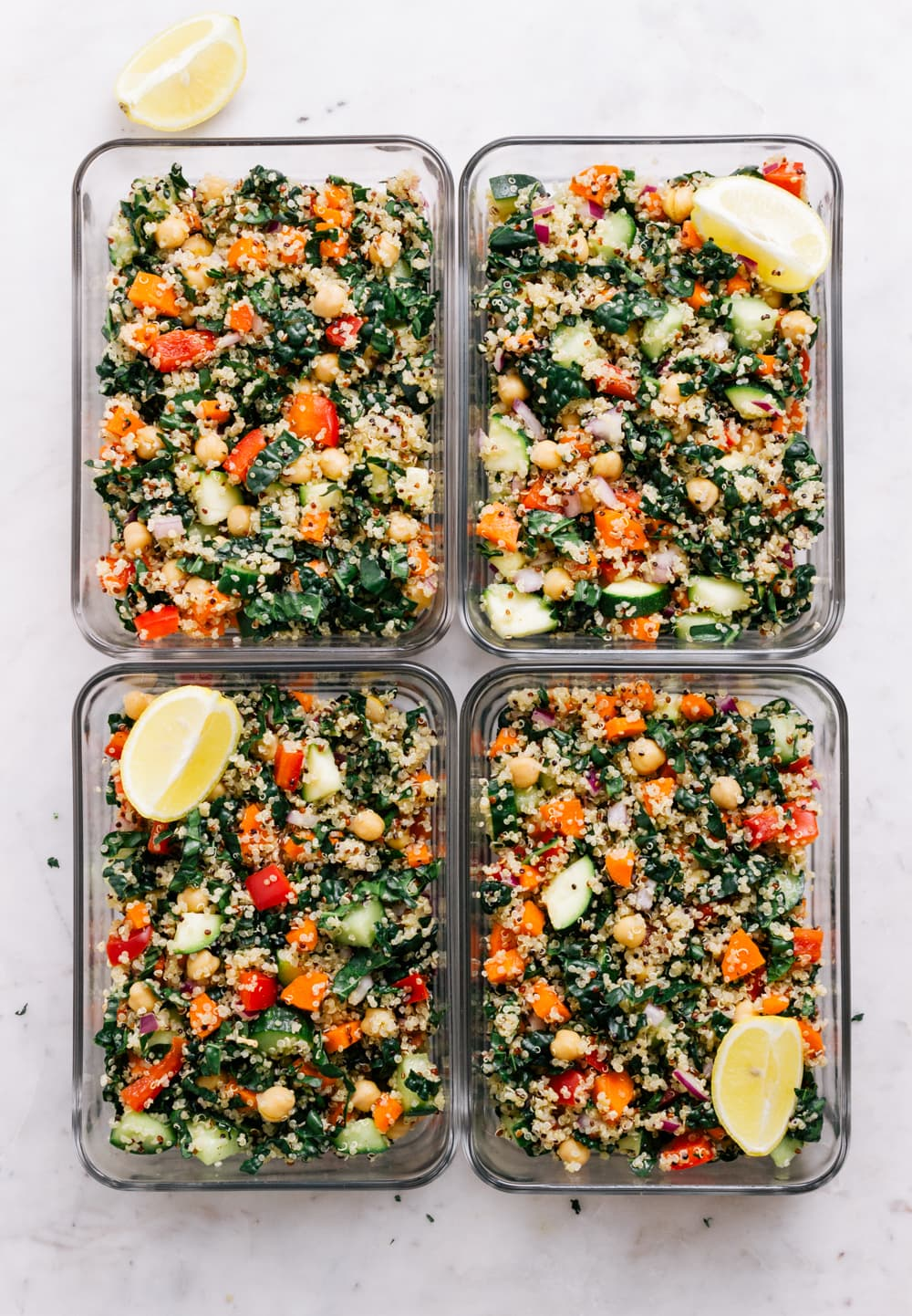 top down view of 4 meal prep containers filled with kale and quinoa salad with lemon wedge.