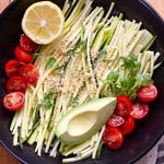 zucchini pasta with tomatoes, avocado, lemon, micro sprouts and almond parmesan in a black bowl on a wooden cutting board