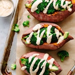 top down view of stuffed baked sweet potatoes with broccoli, avocado and creamy spice cheese sauce on a baking sheet.