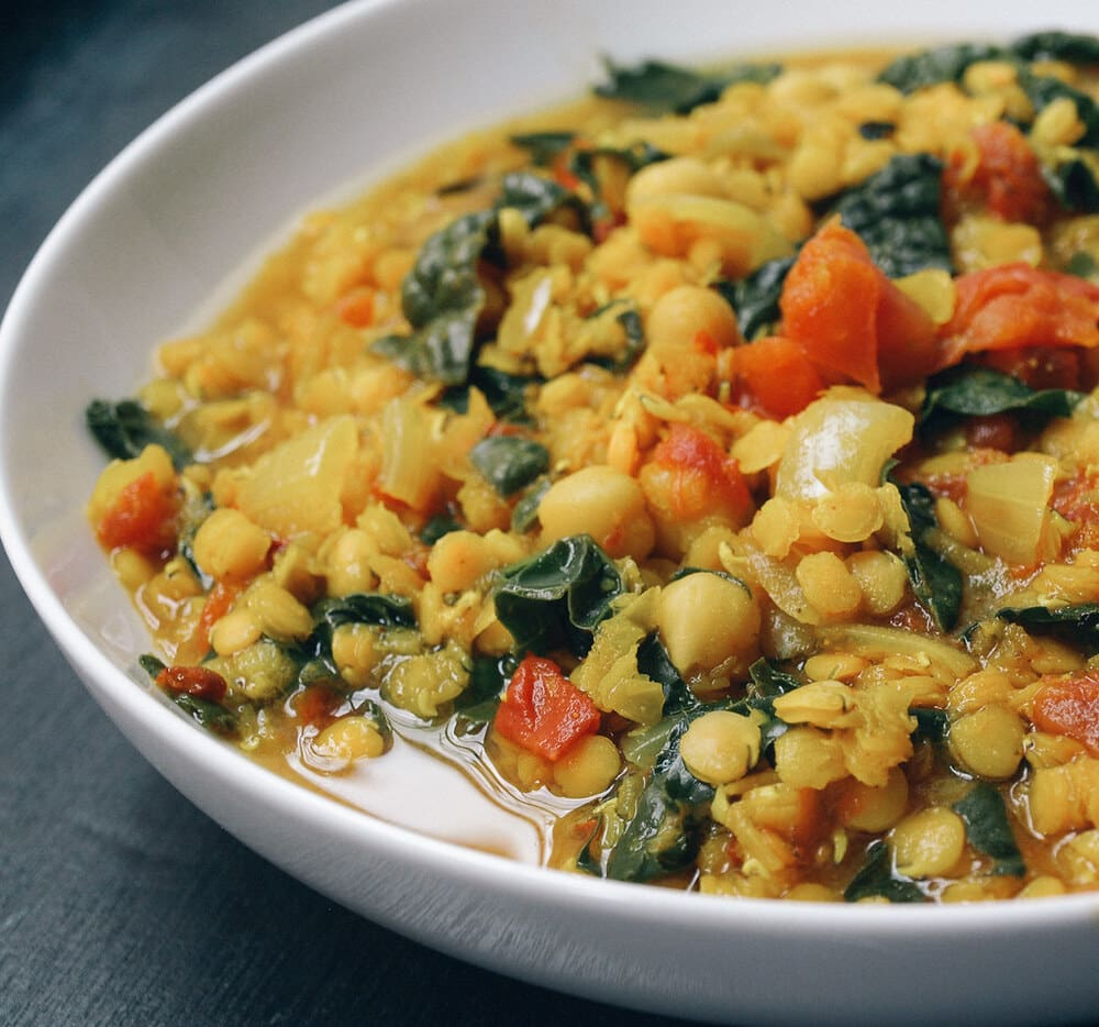 side angle view of curry red lentil stew with chickpeas and kale in a white bowl.