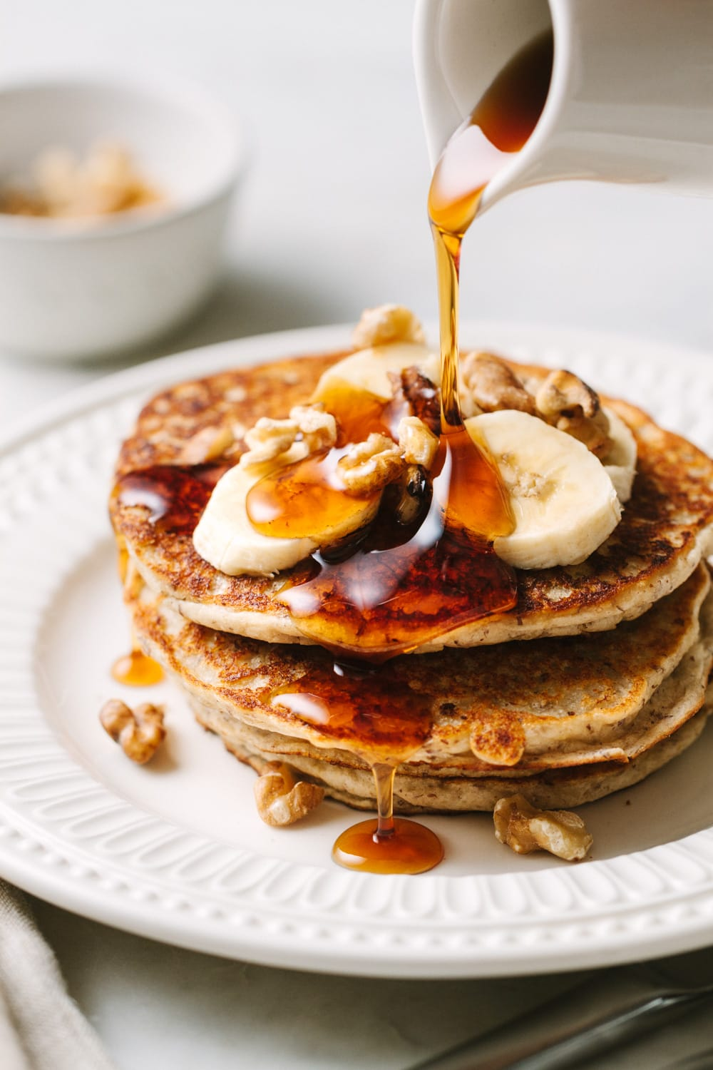 vegan banana pancakes with banana slices and walnuts and drizzled with pure maple syrup on a white plate
