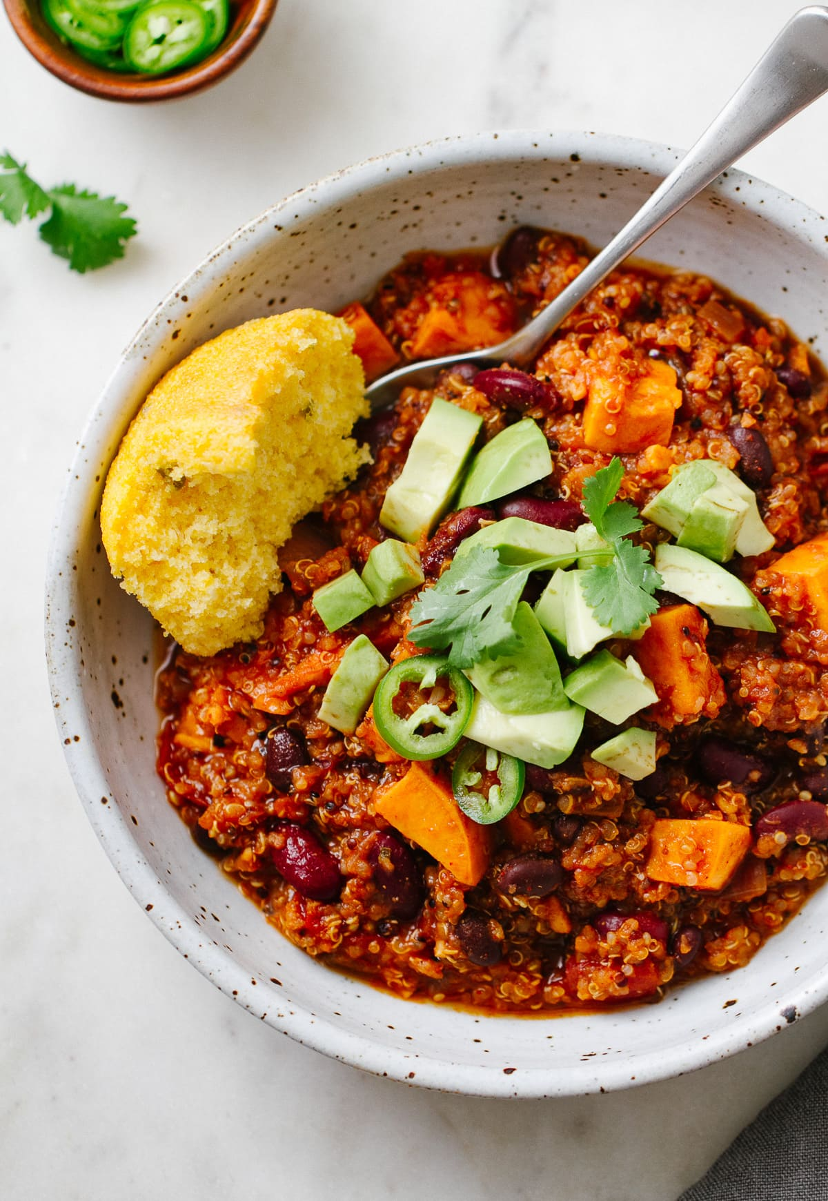 top down view of a bowl with serving of vegan sweet potato quinoa chili with cornbread and spoon.