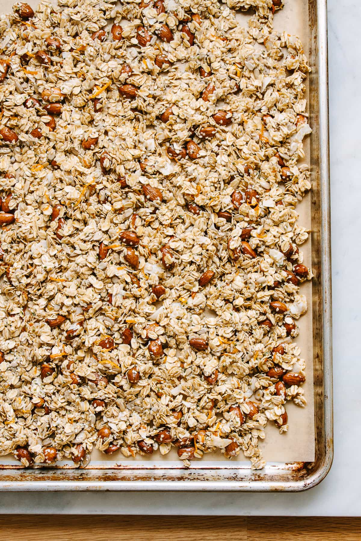 top down view of freshly mixed granola layered on a rimmed baking sheet before baking.