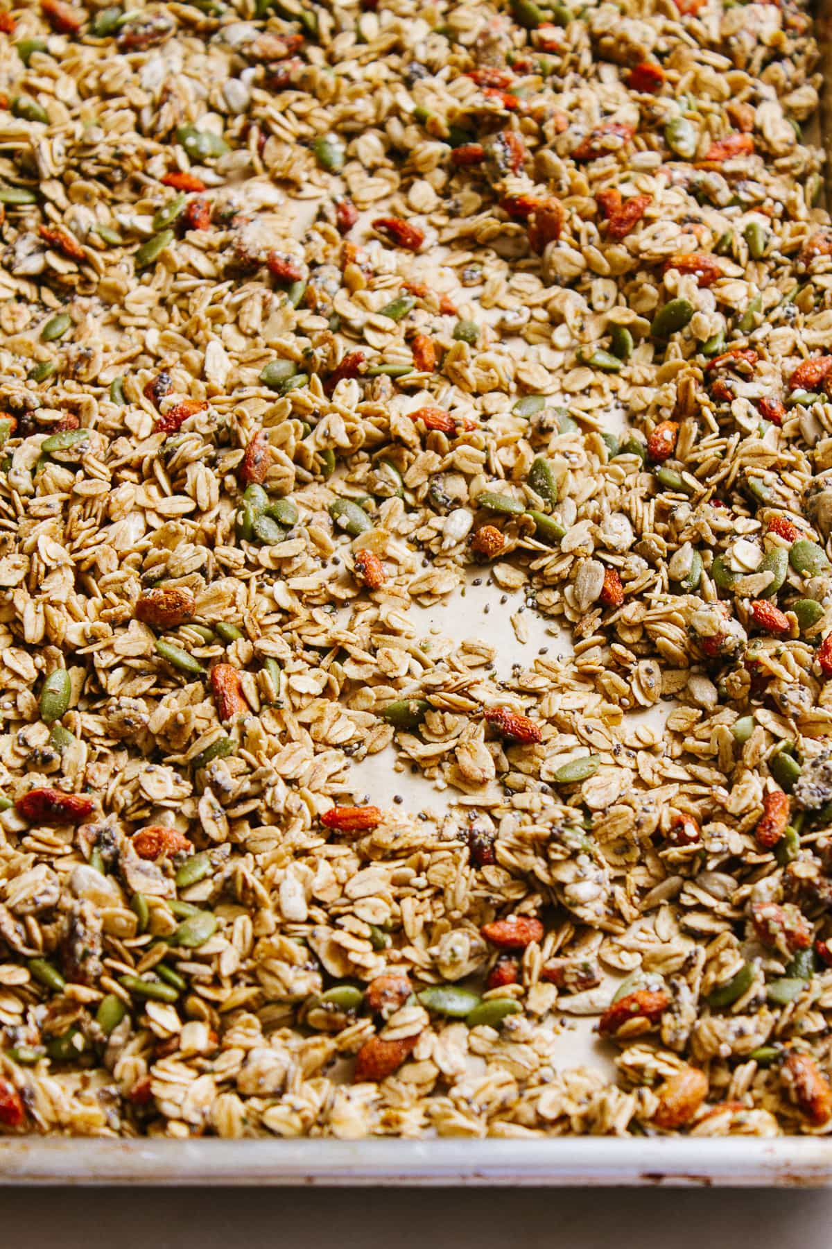 side angle view of freshly made seeds and goji berry granola on a baking sheet.