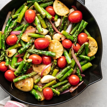 top down view of freshly cooked asparagus and tomato medley in a skillet.