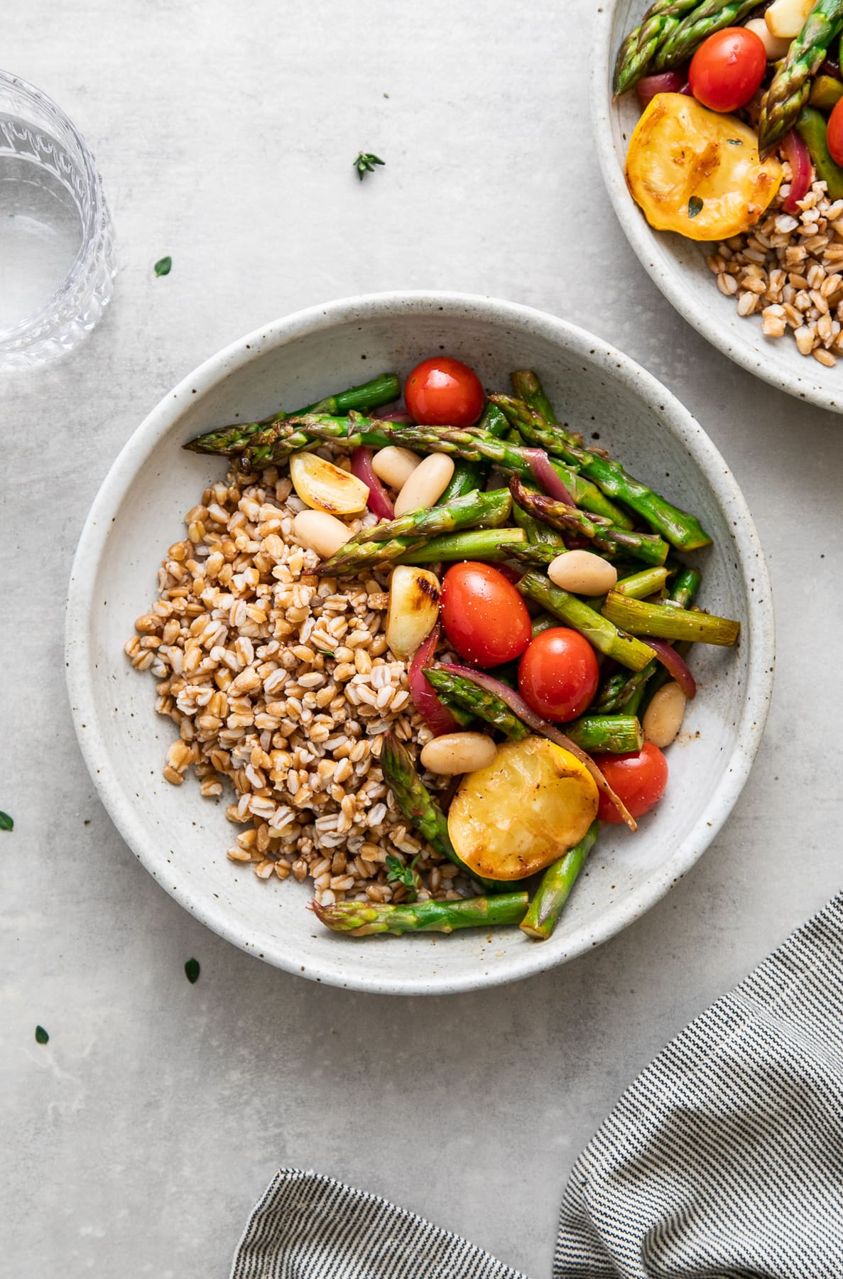 top down view of a bowl with serving of skillet asparagus and tomato medley with farro and items surrounding.
