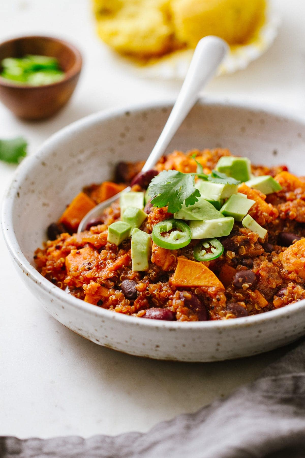 side angle view of a bowl with a serving of healthy vegan sweet potato quinoa chili with spoon.