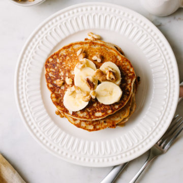 vegan banana pancakes with banana slices and walnuts on a white plate