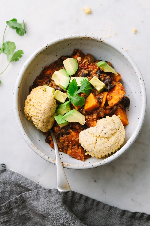 top down view of vegan sweet potato and quinoa chili in a bowl with vegan cornbread.