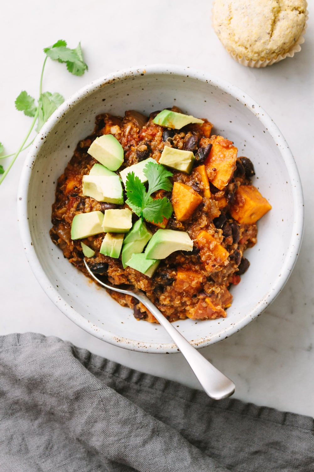 top down view of a bowl with a serving of vegan sweet potato and quinoa chili.