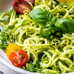 close up, side angle view of zucchini pasta with creamy avocado cucumber sauce, sliced cherry tomatoes, micro sprouts, basil, lemon zest and sliced jalapeno in a white bowl with grey napkin