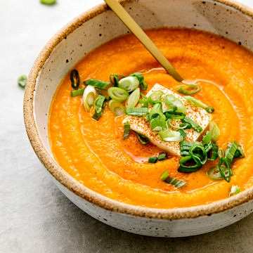 side angle view of carrot miso soup in a bowl with gold spoon.