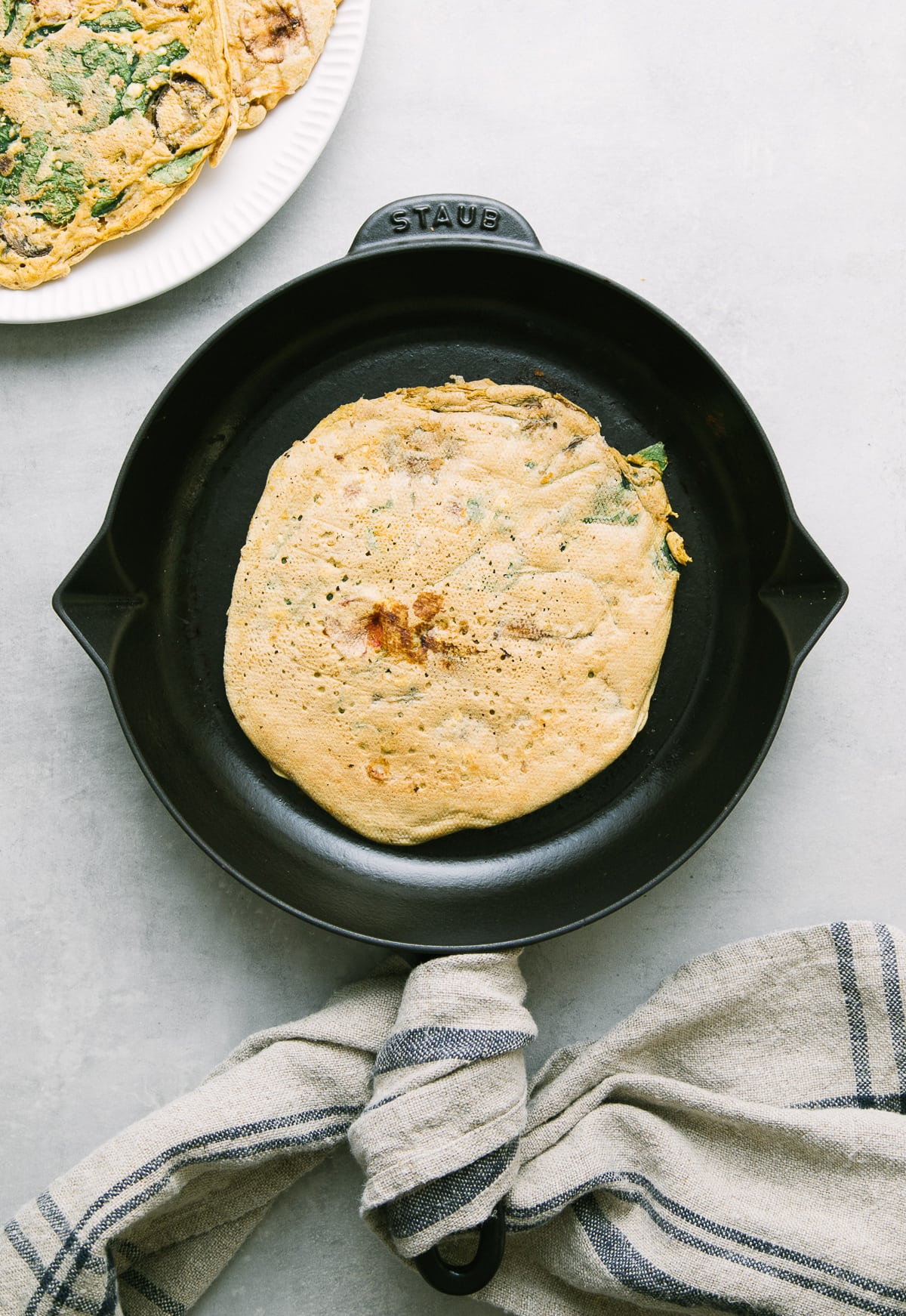 top down view of freshly made gluten free chickpea pancake in a cast iron skillet.