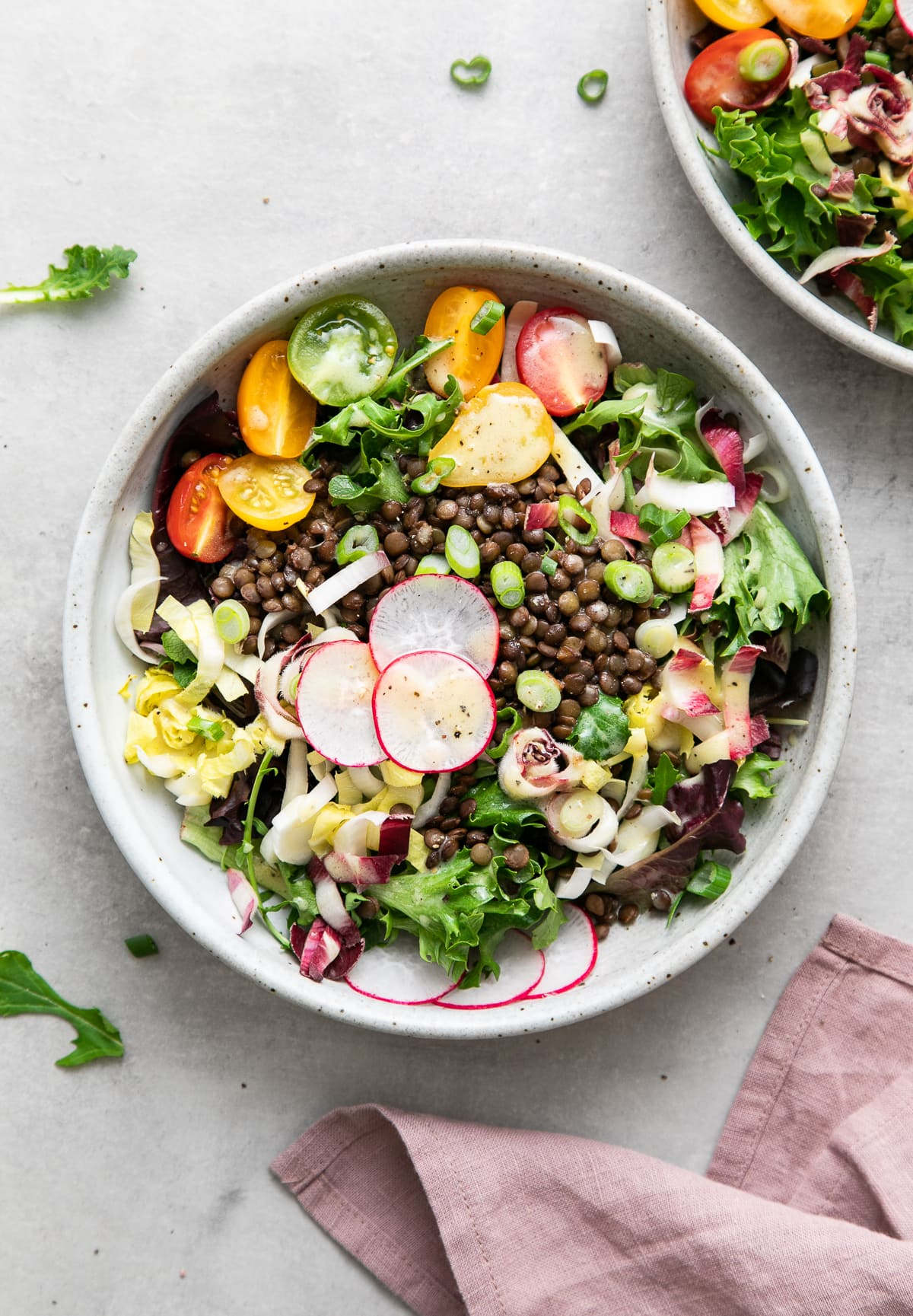 top down view of french lentil and bitter greens salad in a bowl.