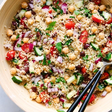 top down view of a large mixing bowl with freshly mixed greek quinoa salad with serving utensils.
