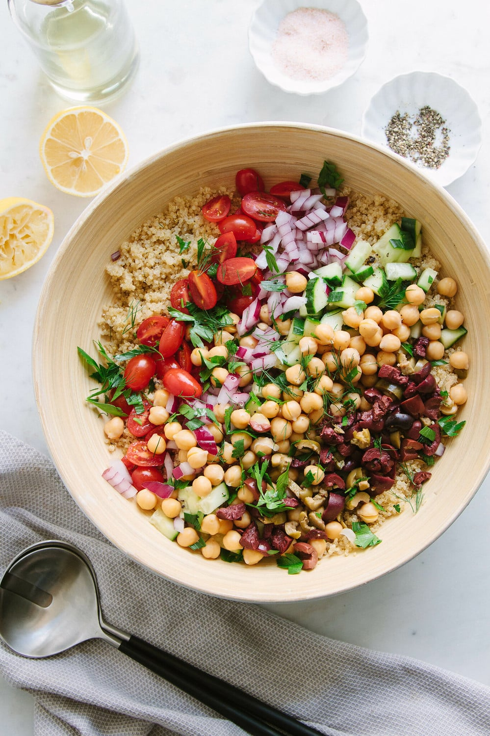 top down view of ingredients for greek quinoa salad added to a large mixing bowl.