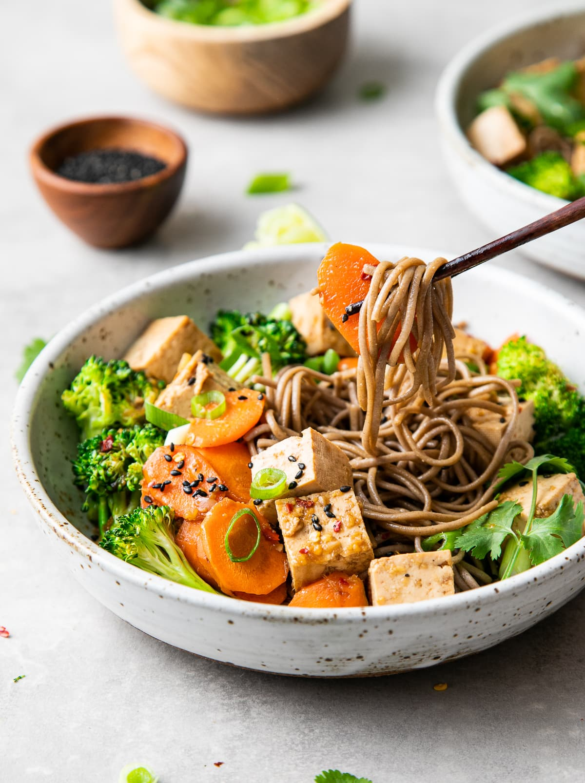 side angle view of chopsticks holding a bite of sesame soba noodle salad with tofu with items surrounding.