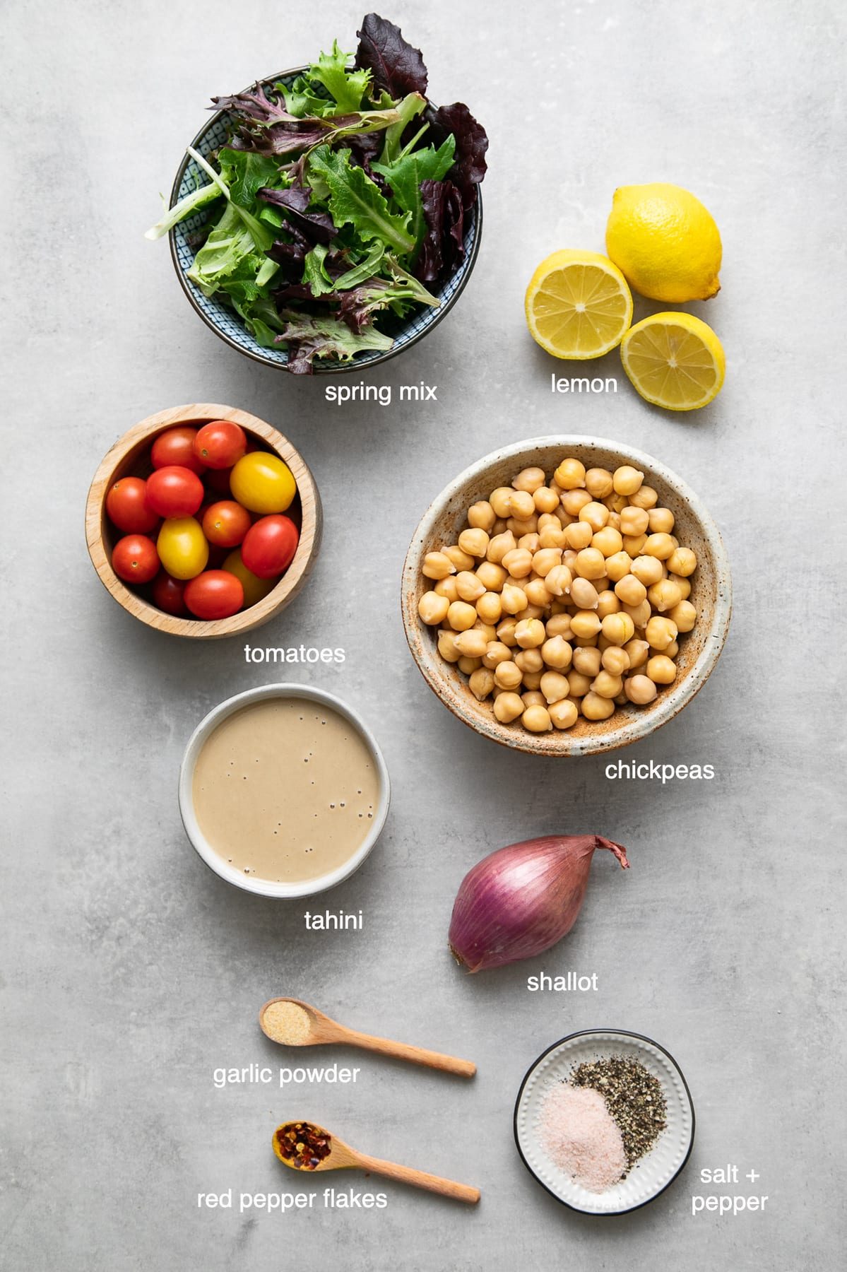 top down view of ingredients used to make green salad with chickpeas and tahini dressing.