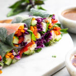 side angle view of sliced summer rolls on a marble serving board with items surrounding.