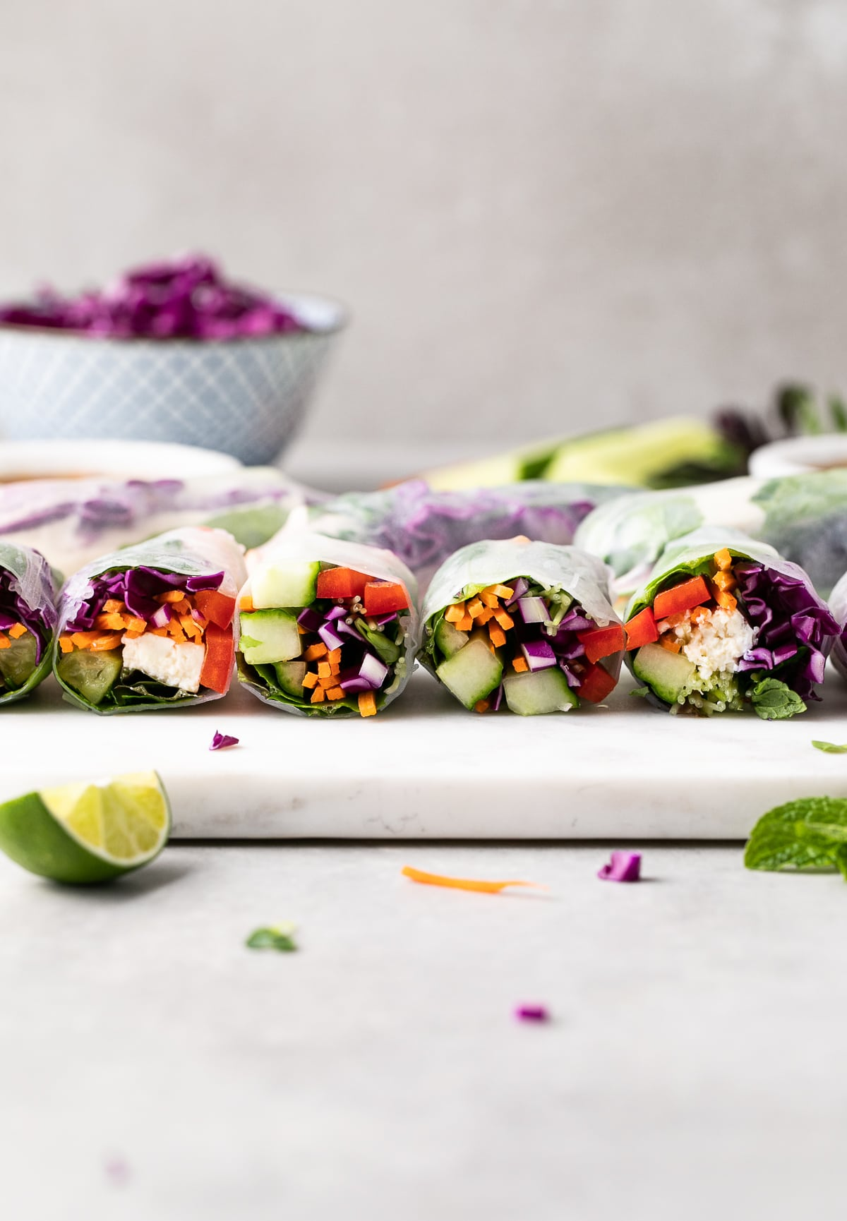 head on view of sliced summer rolls on a marble serving board with items surrounding.