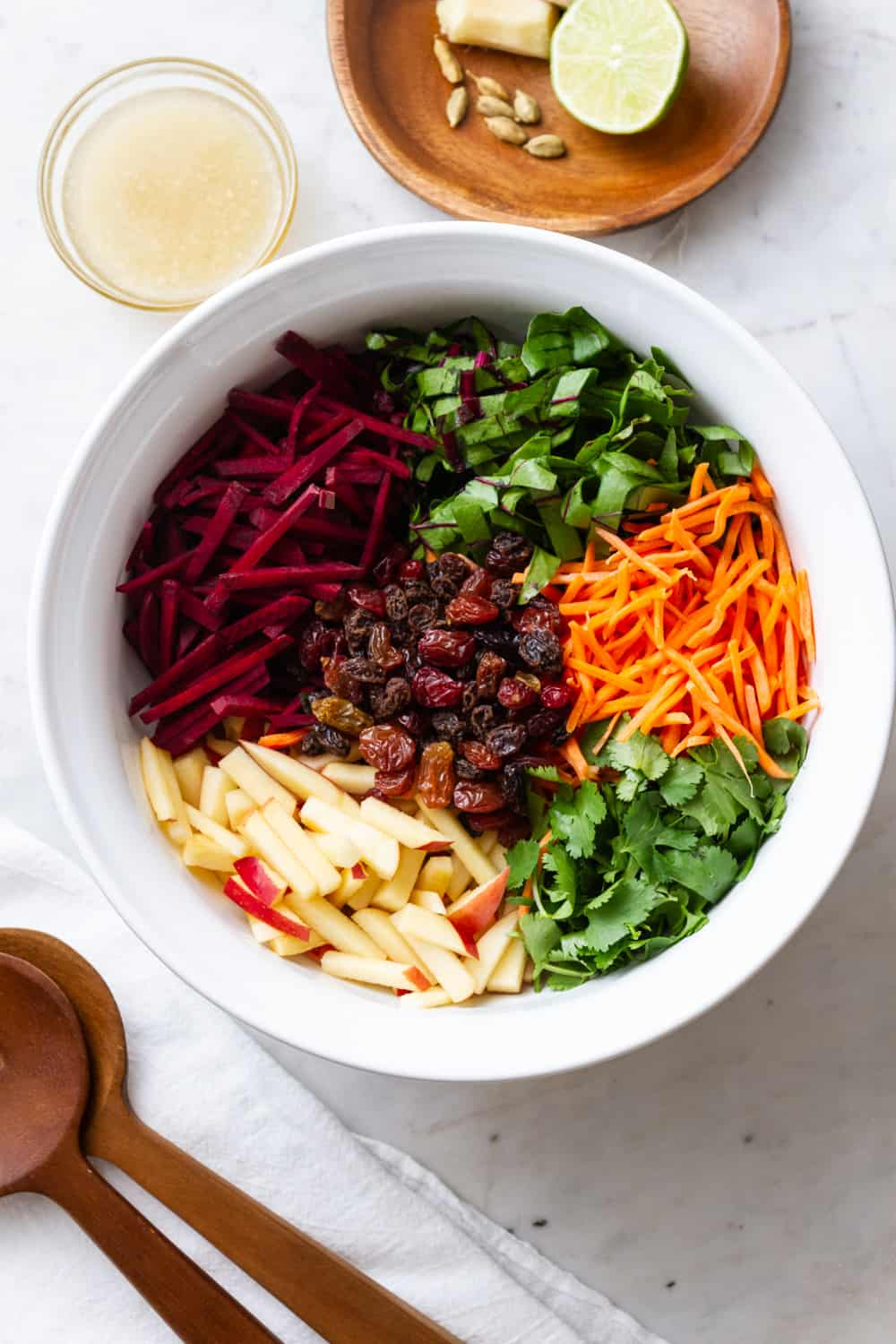 healthy detox salad ingredients added to a white serving bowl
