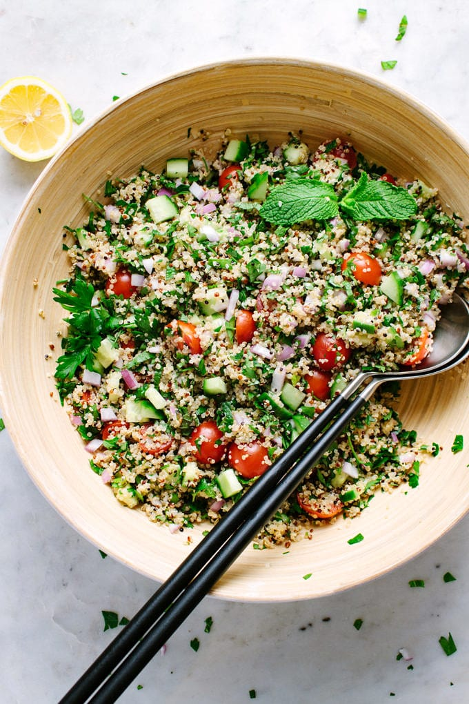 top down view quinoa tabbouleh freshly mixed in a large mixing bowl with serving utensils.