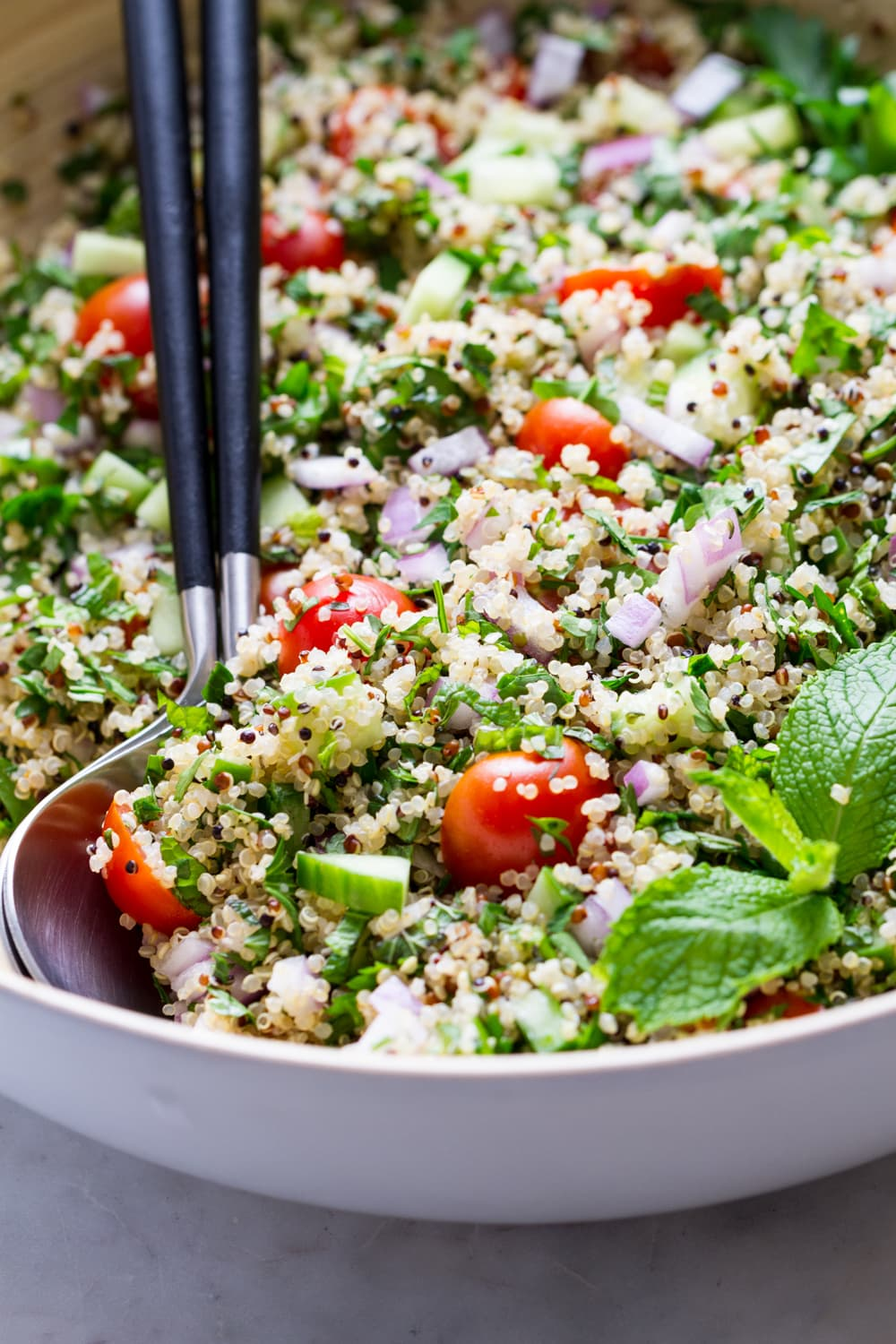up close, side angle view of healthy quinoa tabbouleh in a large mixing bowl with serving utensils.