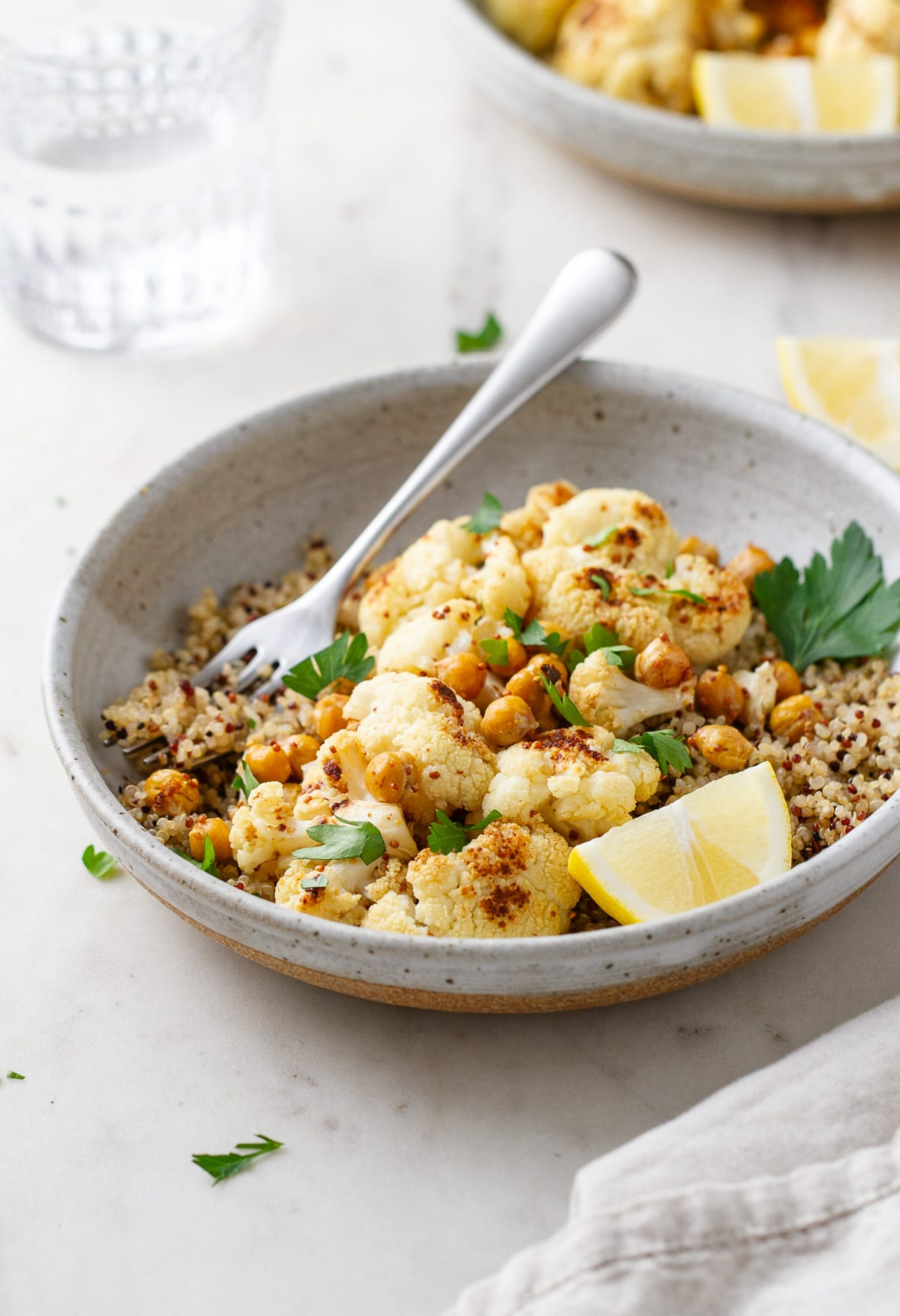 side angle view of a bowl with a serving of quinoa, roasted cauliflower with mustard dressing and chickpeas.