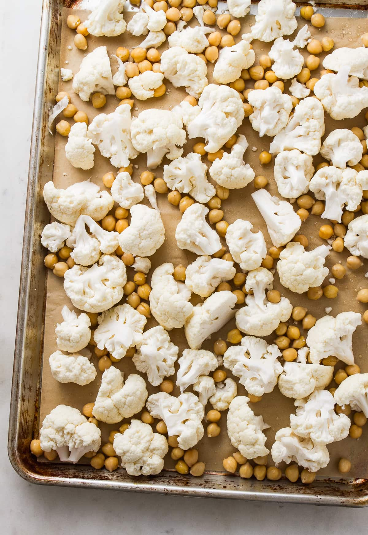 top down view of cauliflower florets and chickpeas on a rimmed baking sheet before roasting.