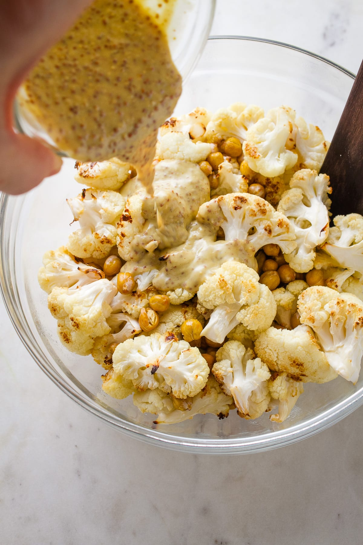 top down view of roasted cauliflower and chickpeas in a glass mixing bowl with mustard dressing poured overtop.