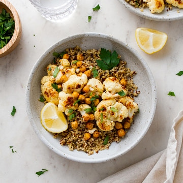 top down view of a bowl with a serving of quinoa, roasted cauliflower with mustard dressing and chickpeas.